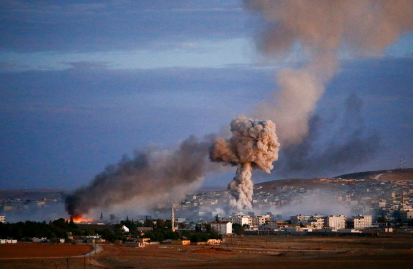 Smoke and flames rise over the Syrian border town of Kobani after an airstrike, October 20, 2014 (photo credit: REUTERS)