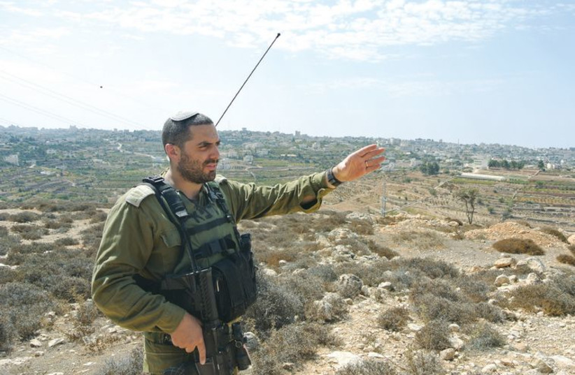 Capt. Eitan Dana-Picard of the Etzion Brigade gestures at an overlook of the town of Halhoul. (photo credit: SETH J. FRANTZMAN)