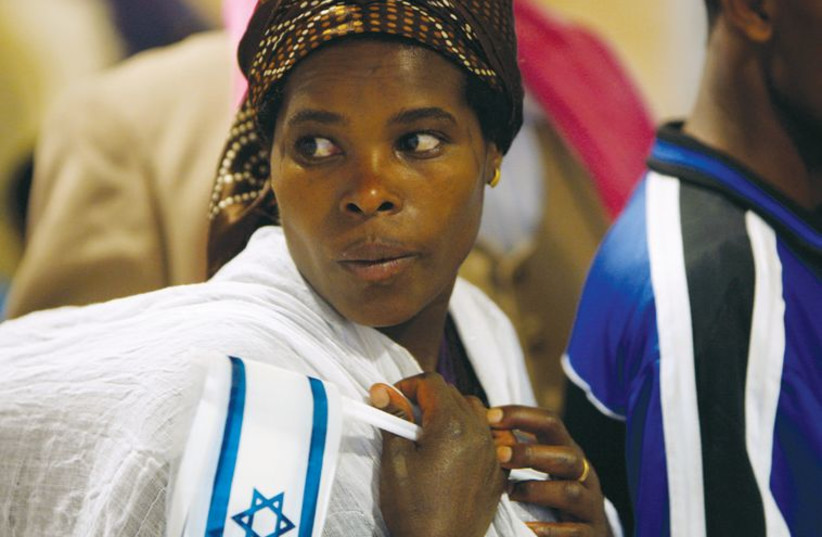 An immigrant from Ethiopia holds an Israeli flag as she carries her child upon her arrival at Ben-Gurion International Airport in January 2011. (photo credit: REUTERS)