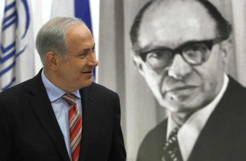 Prime Minister Benjamin Netanyahu walks in front of a poster of the late Prime Minister Menachem Begin upon his arrival at the Likud party meeting at the Menachem Begin Heritage Center in Jerusalem (photo credit: REUTERS)