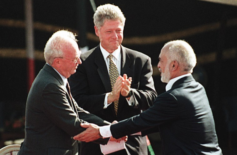 US PRESIDENT Bill Clinton applauds as prime minister Yitzhak Rabin and Jordanian King Hussein shake hands after signing a peace treaty between the countries in the Arava 20 years ago (photo credit: REUTERS)