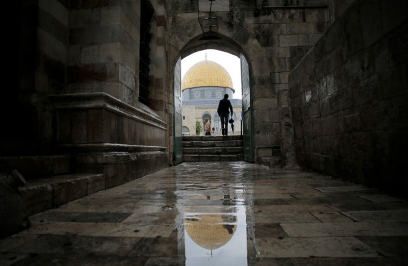 A visitor walks toward the Dome of the Rock as he enters the compound known to Muslims as Noble Sanctuary and to Jews as Temple Mount, in Jerusalem's Old City (photo credit: REUTERS)
