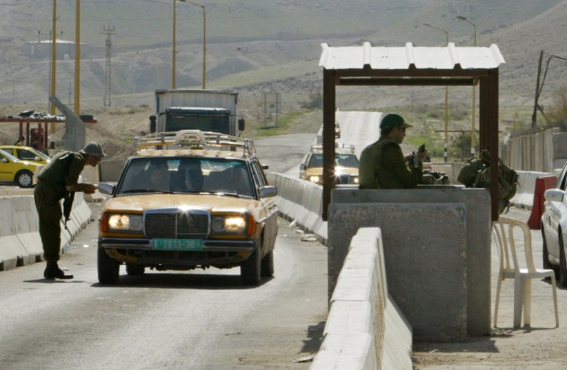 Israeli soldiers check cars at a checkpoint near the West Bank City of Jericho (photo credit: REUTERS)