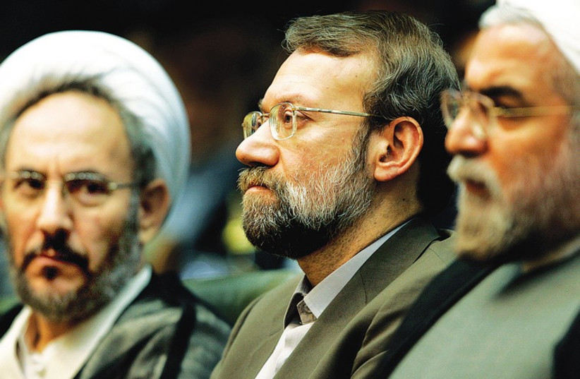 Ali Younesi (center) with President Hassan Rouhani (right) and Ali Larijani, the current chairman of the Iranian parliament, at a conference on Iran's Nuclear Policies and Prospects in Tehran in 2006. (photo credit: RAHEB HOMAVANDI/REUTERS)