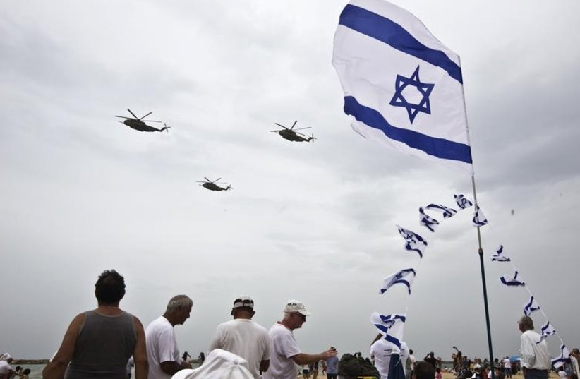 People watch Israeli Air Force planes fly over the Mediterranean Sea from a Tel Aviv beach, during an aerial show as part of celebrations for Israel's Independence Day, marking the 66th anniversary of the creation of the state (photo credit: REUTERS)