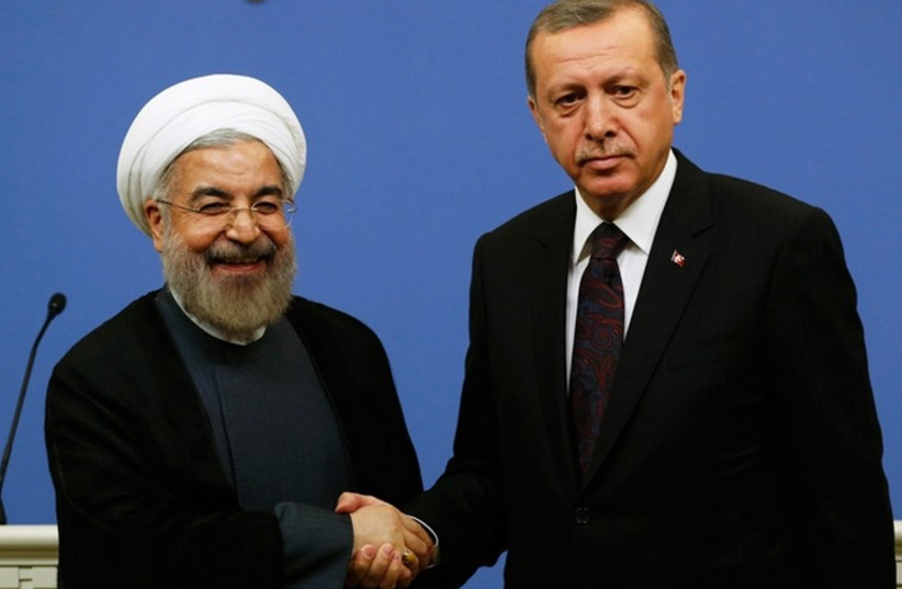 Iran's President Hassan Rouhani shakes hands with Turkish Prime Minister Tayyip Erdogan (photo credit: REUTERS)