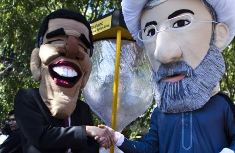 Members of international advocacy group Avaaz take part in a protest wearing masks of Iran's new President Hassan Rouhani (R) and US president Barack Obama, outside the UN headquarters in New York (photo credit: REUTERS)