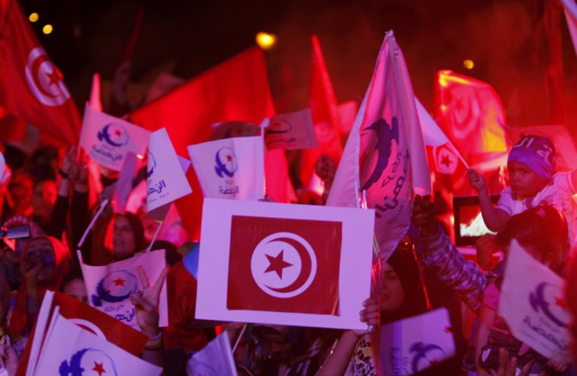 Supporters of the Islamist Ennahda movement wave party flags during a campaign event in Tunis (photo credit: REUTERS)