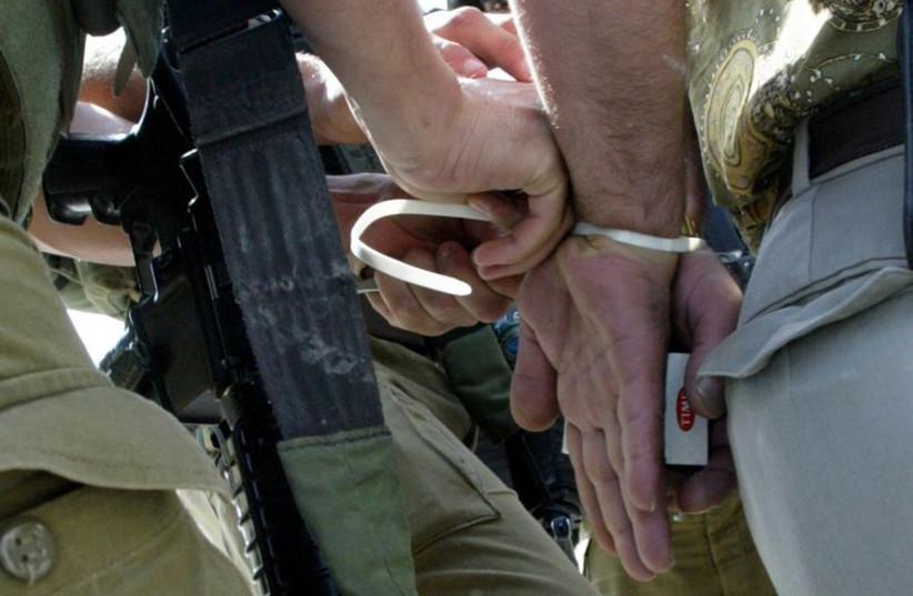 IDF soldier handcuffs a man (photo credit: REUTERS)
