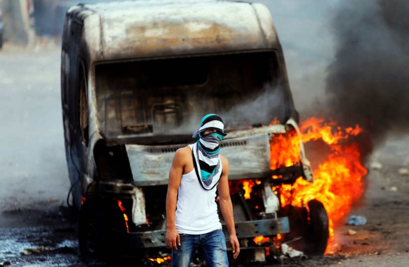 A Palestinian protester stands in front of an Israeli car set torched during clashes with Israeli security forces in east Jerusalem (photo credit: REUTERS)