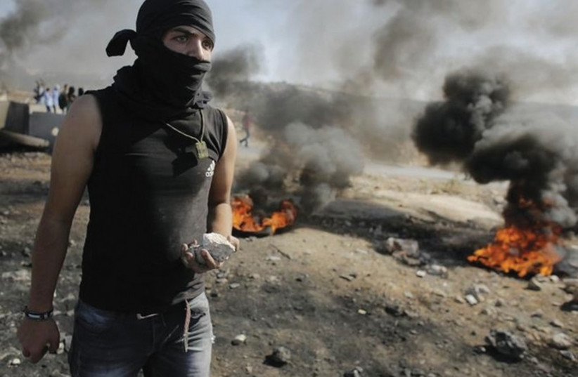 Youth holds stone as Palestinians clash with IDF in the West Bank (photo credit: REUTERS)