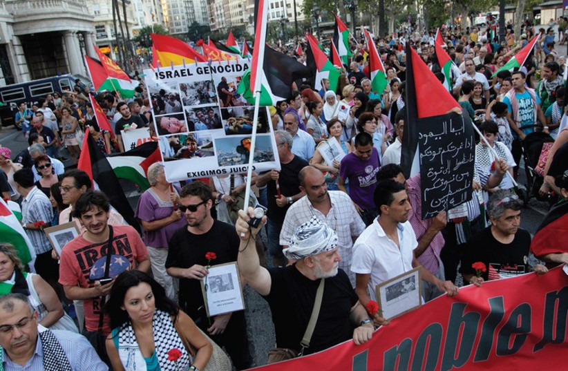 DEMONSTRATORS MARCH with Palestinian flags during a protest against the Israeli offensive against Gaza, in Valencia, Spain (photo credit: REUTERS)