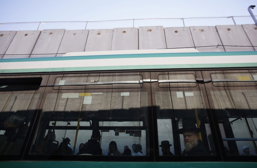 Jewish worshippers board a bus next to a section of the controversial Israeli barrier after visiting Rachel's Tomb in Bethlehem (photo credit: REUTERS)