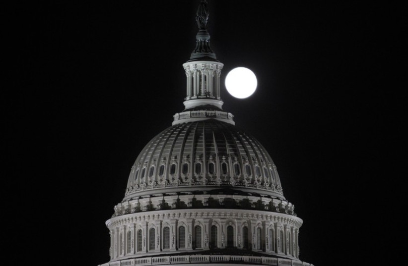 The full moon rises behind the US Capitol Dome in Washington  (photo credit: REUTERS)