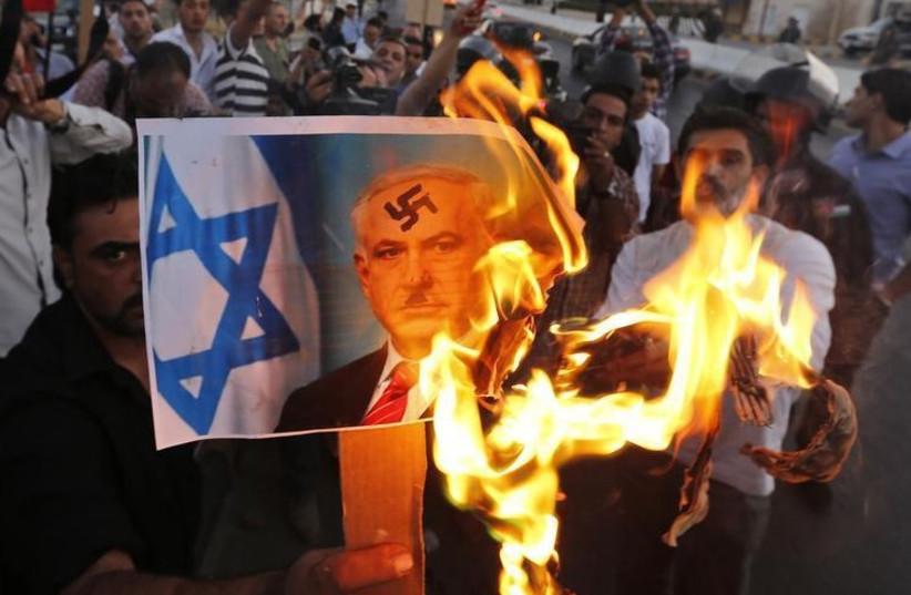 Jordanian opposition members burn a picture of Prime Minister Binyamin Netanyahu in Amman (photo credit: REUTERS)