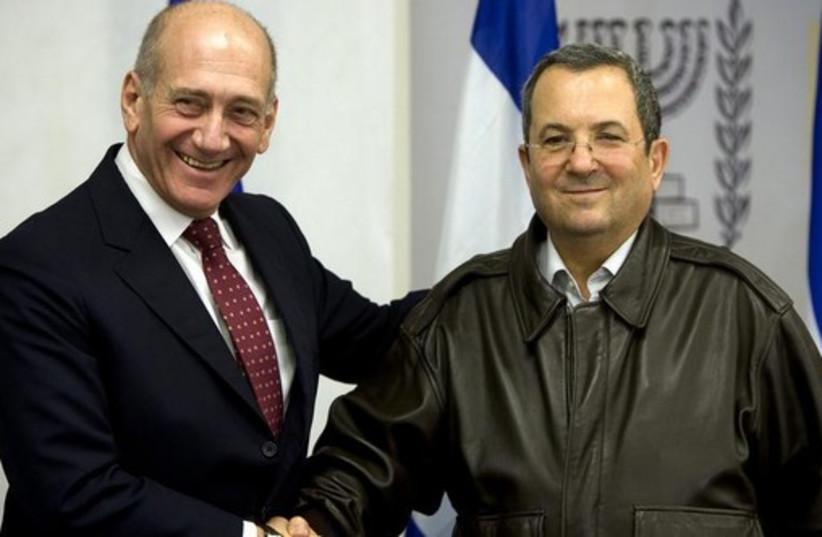 Former prime minister Ehud Olmert (L) shakes hands with his defense minister, Ehud Barak (photo credit: REUTERS)