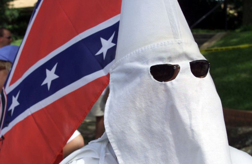 Ku Klux Klan members approach the Walls Unit in Huntsville, Texas. (photo credit: REUTERS)