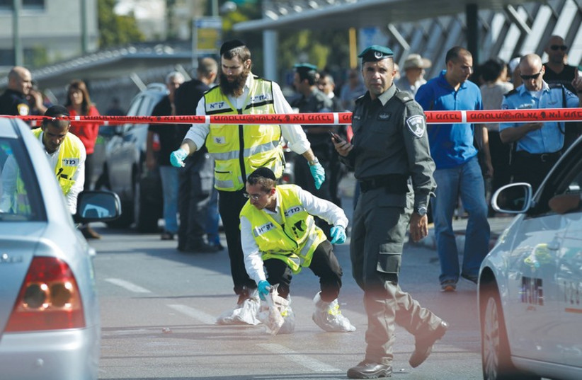 ZAKA SEARCH AND RECOVERY organization members and a border policeman work at the scene of yesterday's attack near the Hagana train station in south Tel Aviv (photo credit: REUTERS)
