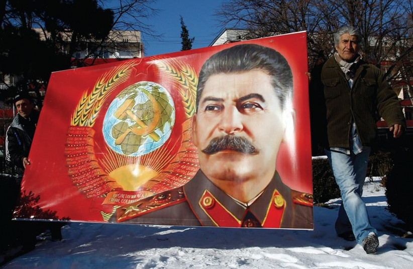 PEOPLE CARRY a poster with a portrait of late Soviet dictator Josef Stalin (photo credit: REUTERS)