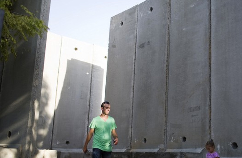 A resident of Nahal Oz walks next to a concrete wall to protect the local kindergarten, just outside the northern Gaza Strip  (photo credit: REUTERS)