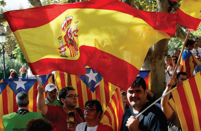PEOPLE WAVE Spanish and Catalan flags in Barcelona in September (photo credit: REUTERS)