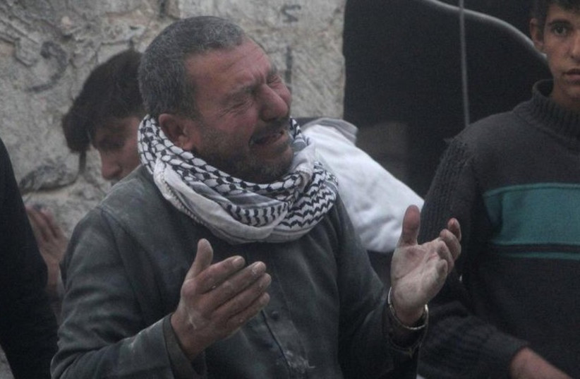 A Syrian man reacts after oppositionists say pro-Assad forces dropped a bomb on a neighborhood in Aleppo (photo credit: REUTERS)