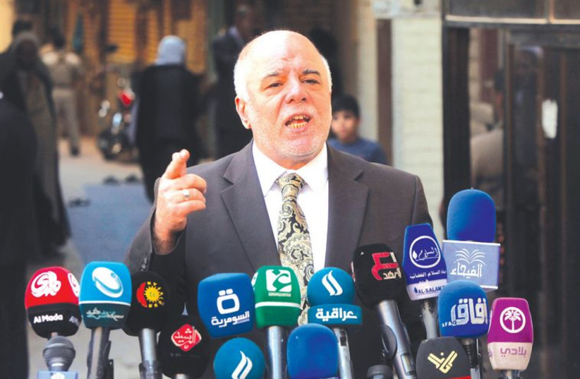 Iraqi Prime Minister Haider al-Abadi speaks at a news conference during his visit to Najaf, south of Baghdad, (photo credit: REUTERS)