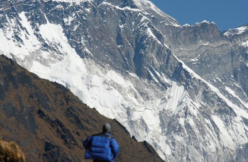A TOURIST looks at a view of Mount Everest from the hills of Syangboche in Nepal (photo credit: REUTERS)