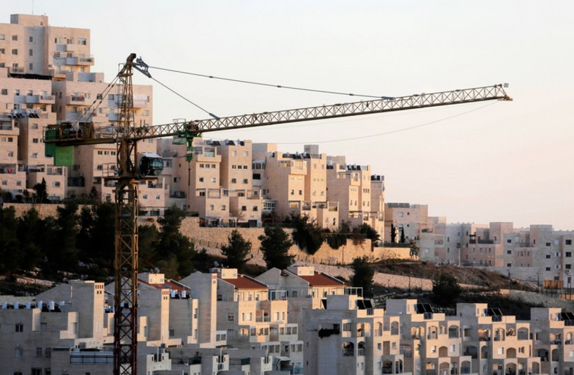A crane is seen next to Har Homa in Jerusalem (photo credit: REUTERS)