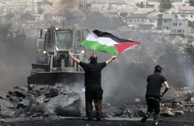 A protester holds a Palestinian flag in front of an IDF bulldozer in the West Bank [File] (photo credit: REUTERS)