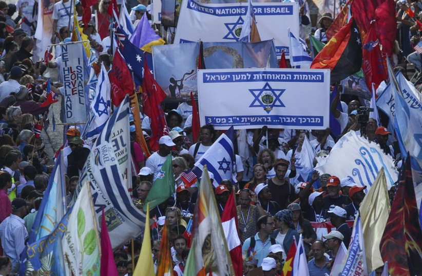 Evangelical Christians from around the world wave their national flags along with Israeli flags as they march in a parade in Jerusalem to mark the Feast of Tabernacles  (photo credit: JNS.ORG)
