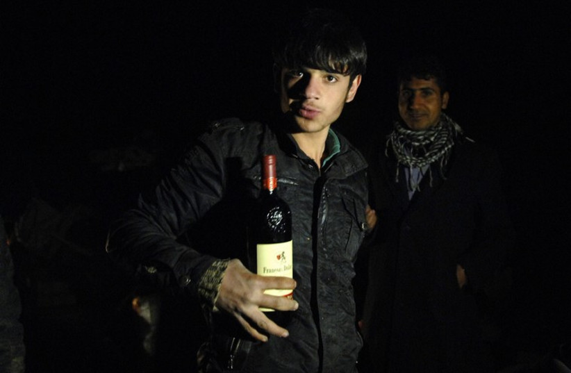 A smuggler poses with a bottle of wine during an alcohol smuggling operation to Iran (photo credit: REUTERS)