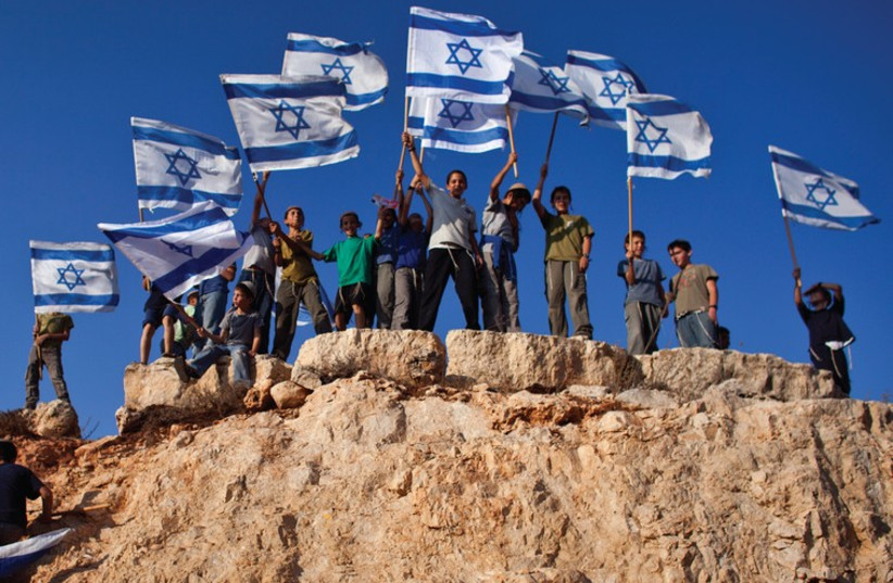 Jewish Youths in Israel wave flags and stand atop a hill. The author recalls his own young days in Zionist youth groups. (photo credit: REUTERS)