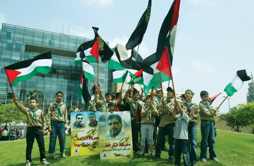 Palestinian members of a youth group wave their national flags and hold posters depicting portraits of Palestinian prisoners during a protest in solidarity with them. (photo credit: REUTERS)