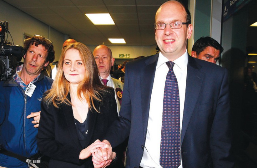 United Kingdom Independence Party (UKIP) candidate Mark Reckless, the former Conservative Party member of Parliament for Rochester and Strood, and his wife Catriona Brown, arrive for the by-election ballot count at Medway Park in Gillingham, southeast England in November. (photo credit: REUTERS)