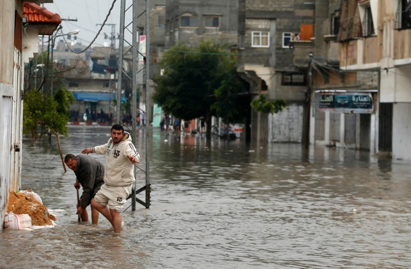 Palestinians place sandbags as they try to prevent rain water from flooding their house following heavy rain in Gaza City November 27 (photo credit: REUTERS)