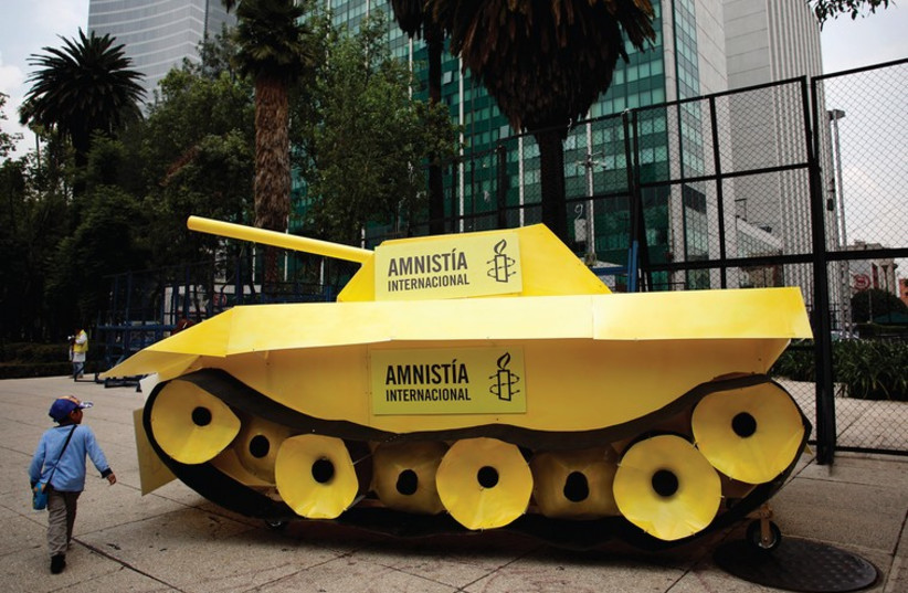 A child walks around a fake tank parked outside the US embassy during a protest held by Amnesty International in Mexico City. (photo credit: REUTERS)