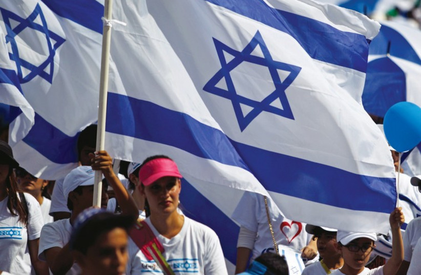 People carry Israeli flags during a Jerusalem Day march in the capital. (photo credit: REUTERS)