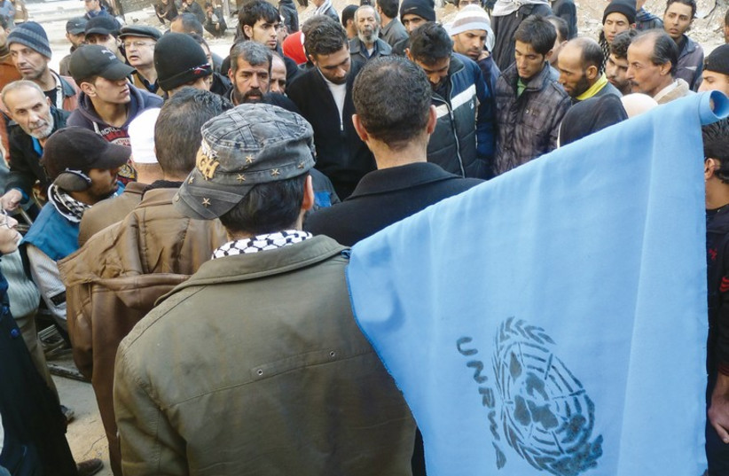 A man with an UNRWA flag in the southern Gaza Strip. (photo credit: REUTERS)
