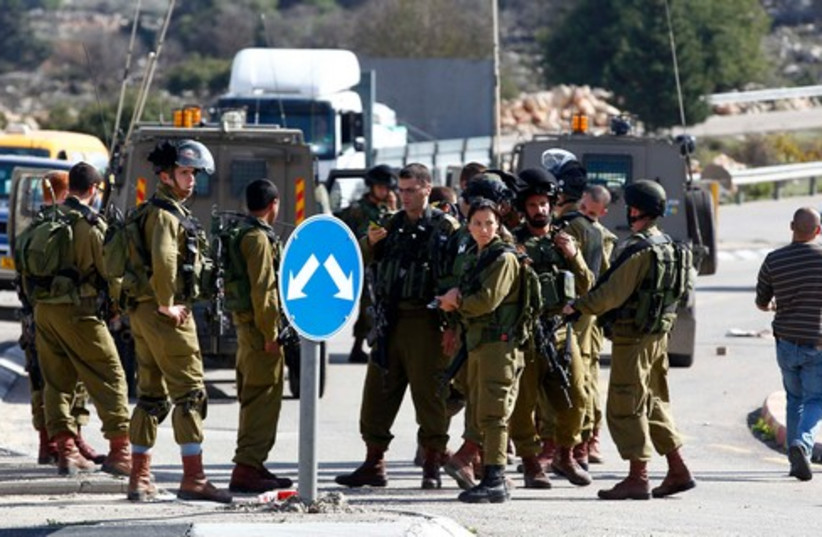 IDF soldiers at the scene of a stabbing attack in Gush Etzion, December 1, 2013. (photo credit: REUTERS)