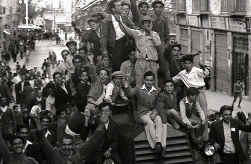 Jews crowd onto a British army armoured car as they celebrate in downtown Jerusalem the morning after the United Nations voted on November 29, 1947 to partition Palestine which paved the way for the creation of the State of Israel on May 15, 1948.  (photo credit: REUTERS)