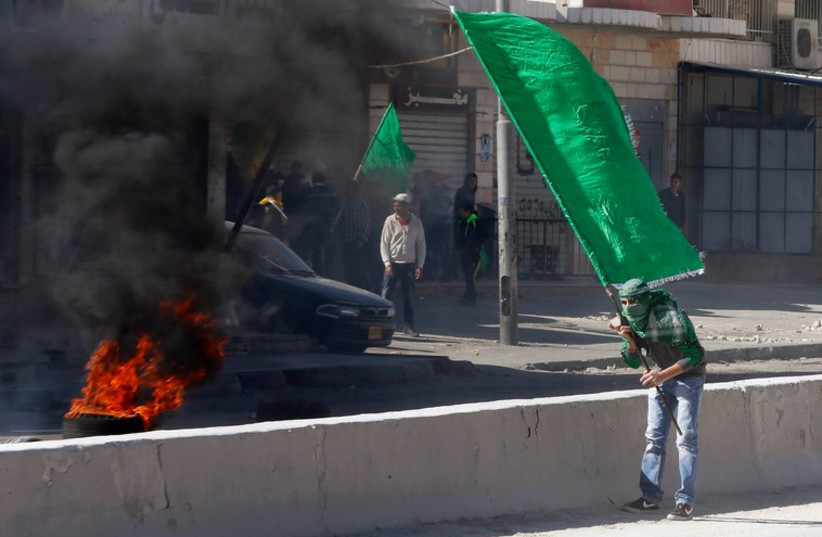 A Palestinian protester holds a Hamas flag during clashes with Israeli troops in the West Bank  (photo credit: REUTERS)