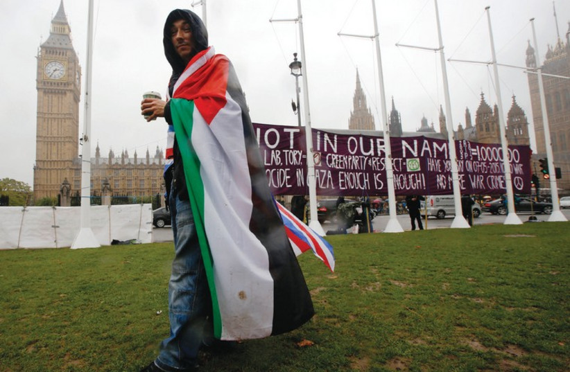 A Palestinian supporter wears Palestinian and Union Jack flags outside the Parliament in London during October's vote on recognizing a state of Palestine (photo credit: REUTERS)