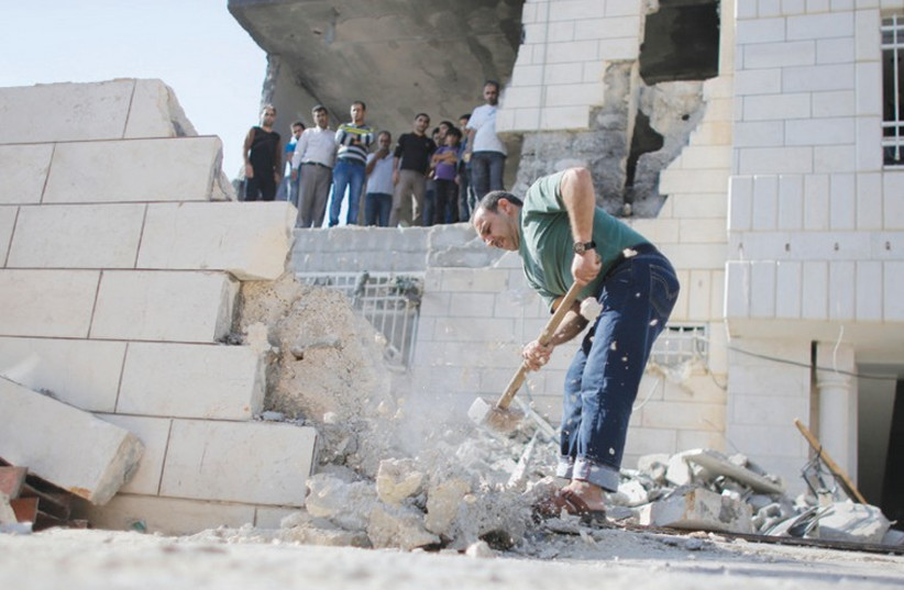 A PALESTINIAN removes a wall to allow a bulldozer access to clear the rubble at the home of Amer Abu Aysha in Hebron in August. The IDF earlier destroyed the home of Abu Aysha, one of the two main suspects in the June kidnapping and murder of three teenagers. (photo credit: AMMAR AWAD / REUTERS)