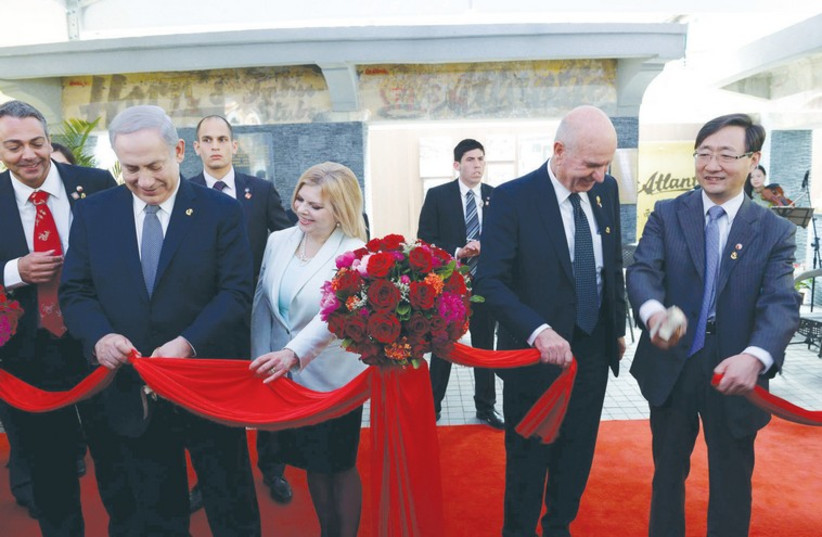 Benjamin Netanyahu, his wife Sara, and Israeli Ambassador to China Matan Vilnai cut the ribbon at an opening ceremony for a coffeehouse at the Shanghai Jewish Refugees Museum. (photo credit: AVI OHAYON - GPO)