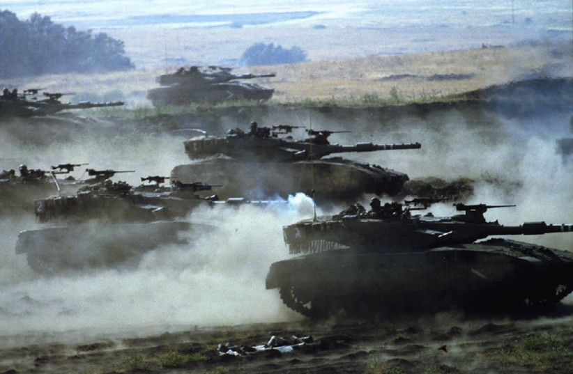 Israeli army Merkava tanks churn up dust as they race towards targets during a live-fire exercise (photo credit: REUTERS)