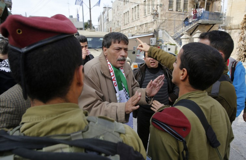 Palestinian Authority Minister Ziad Abu Ein argues with IDF soldiers in Hebron, November 29, 2014 (photo credit: REUTERS)