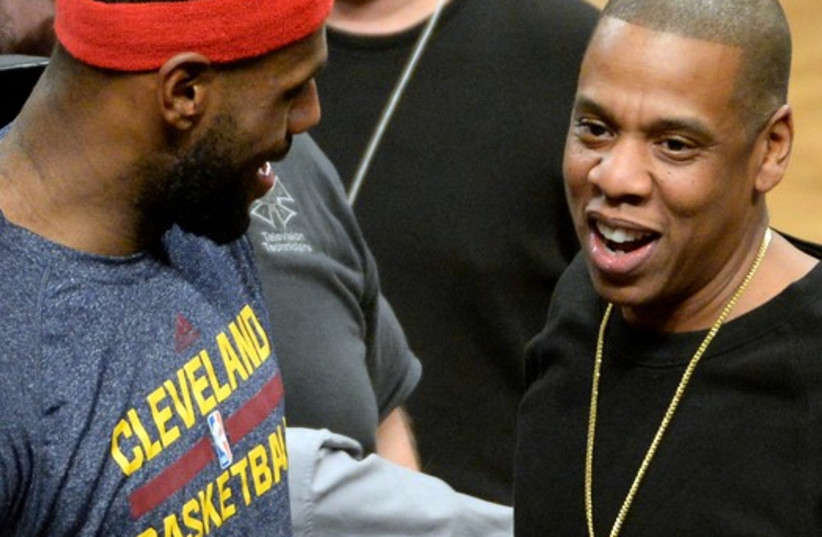 LeBron James (left) talks with Jay Z (right) during the game against the Brooklyn Nets at Barclays Center. (photo credit: REUTERS)