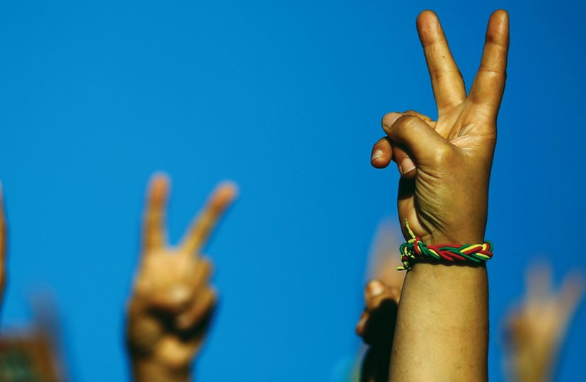 PEOPLE HOLD up peace signs. But who wants peace more – Israel or the Palestinians? (photo credit: REUTERS)