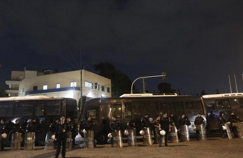Riot police stand guard outside the Israeli embassy in Athens in 2012 (photo credit: REUTERS)